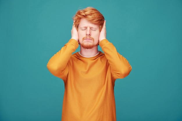 Zirytowany młody rudy mężczyzna z brodą, który ma zamknięte oczy i zakrywa uszy rękami na niebiesko