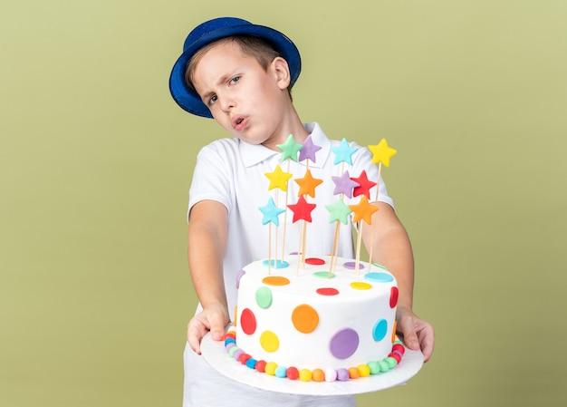 Zirytowany młody słowiański chłopiec z niebieskim kapeluszem strony, trzymając tort urodzinowy na białym tle na oliwkowej ścianie z miejsca na kopię
