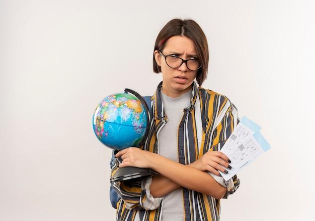 Zirytowany młody student dziewczyna w okularach iz powrotem worek trzymając bilety lotnicze i kula ziemska patrząc z boku na białym tle na biały z miejsca na kopię