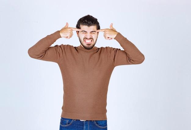 Zirytowany model młodego mężczyzny trzymający palce na skroniach.