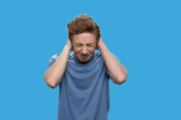 Zirytowany nastolatek zamyka uszy rękami