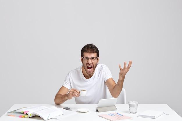 Zirytowany nieogolony mężczyzna denerwuje się wieloma zadaniami i terminami