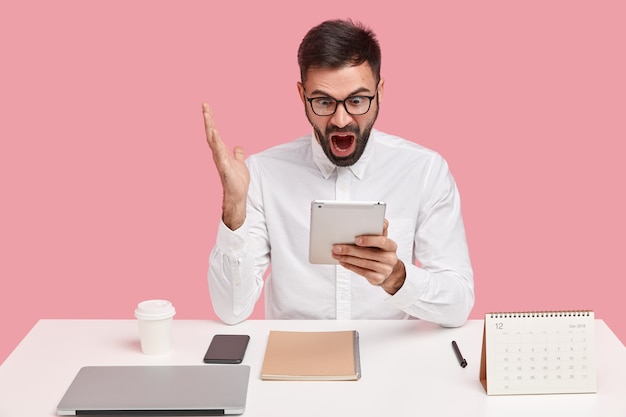 Zirytowany nieogolony mężczyzna krzyczy ze złością, gestykuluje ręką, skupiony na ekranie touchpada, czyta negatywne wiadomości, ubrany formalnie