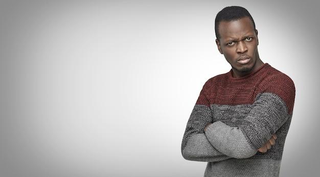 Zirytowany niewierzący afrykański mężczyzna w swobodnym swetrze, patrzący z podejrzliwym wyrazem twarzy