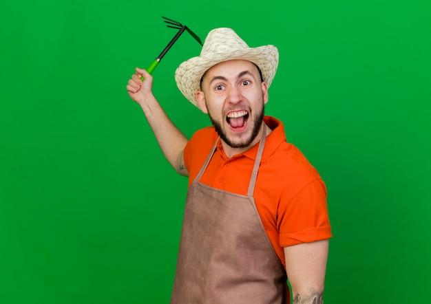 Zirytowany ogrodnik mężczyzna w kapeluszu ogrodniczym posiada grabie motyka