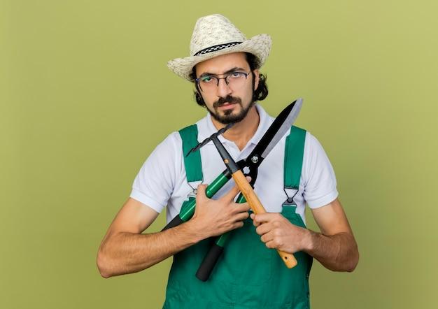 Zirytowany ogrodnik mężczyzna w okularach optycznych w kapeluszu ogrodniczym trzyma i przecina maszynki do strzyżenia i grabie