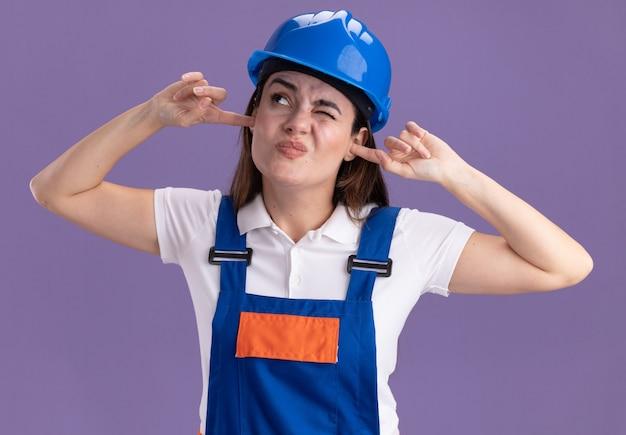 Zirytowany, patrząc na młode kobiety konstruktorów w jednolitych zamkniętych uszach odizolowanych na fioletowej ścianie