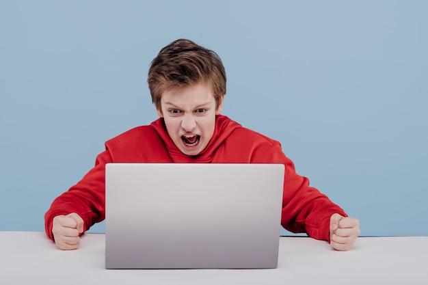 Zirytowany preteen chłopak denerwuje się podczas gry komputerowej w studio na niebieskim tle