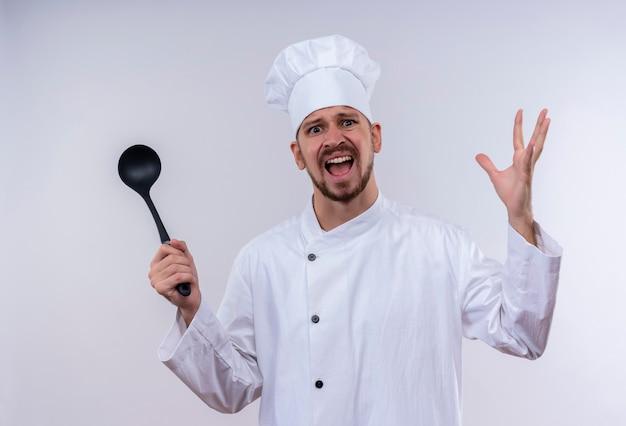 Zirytowany profesjonalny kucharz męski w białym mundurze i kapeluszu kucharskim trzymający chochlę podnoszący ręce z agresywnym wyrazem rozdrażnienia stojący na białym tle