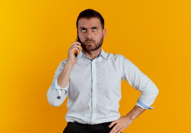 Zirytowany przystojny mężczyzna rozmawia przez telefon patrząc w górę na białym tle na pomarańczowej ścianie