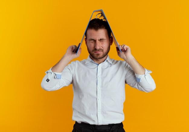 Zirytowany przystojny mężczyzna trzyma folder plików nad głową z zamkniętymi oczami na białym tle na pomarańczowej ścianie