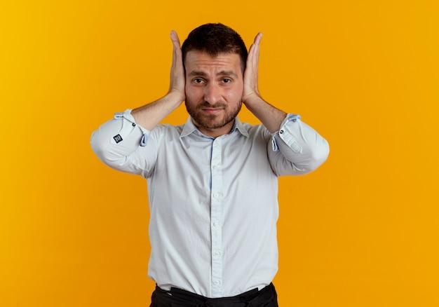Zirytowany przystojny mężczyzna zamyka uszy na białym tle na pomarańczowej ścianie