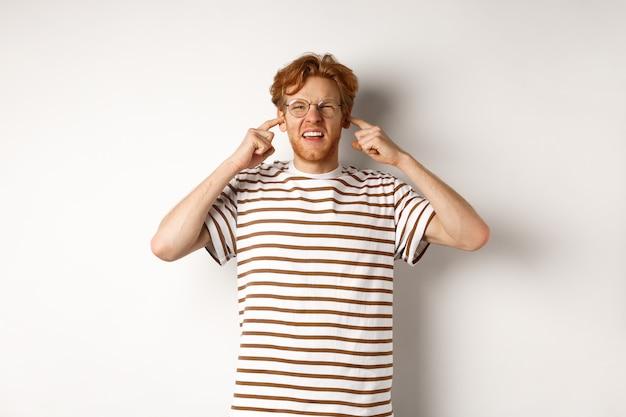 Zirytowany rudy facet w okularach zatykający uszy i narzekający na głośny hałas, zły na hałaśliwych sąsiadów, stojących na białym tle.