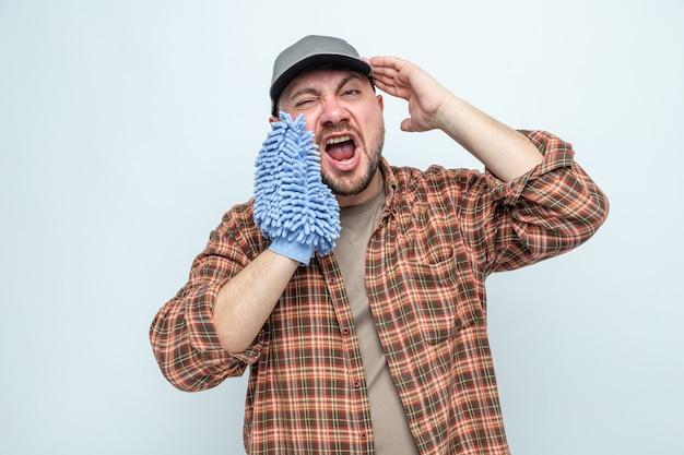 Zirytowany słowiański sprzątacz trzyma rękawiczkę do czyszczenia z mikrofibry blisko ust i krzyczy na kogoś patrzącego z przodu