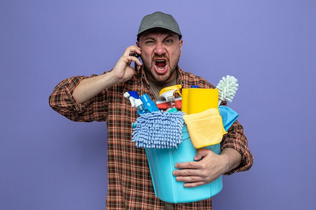 Zirytowany słowiański sprzątacz trzymający sprzęt do sprzątania i krzyczący na kogoś przez telefon