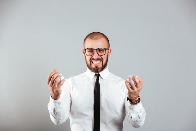 Zirytowany szalony biznesmen w białej koszuli i okularach zgniatających papiery w obu kulkach, odizolowane na szarej ścianie