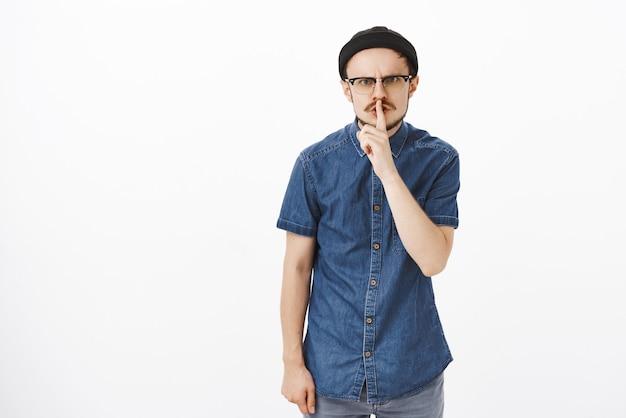 Zirytowany wkurzony zły facet z brodą w czapce i okularach marszczący brwi z niezadowolonym, szalonym spojrzeniem proszący o ciszę i nie przerywanie próby zespołu