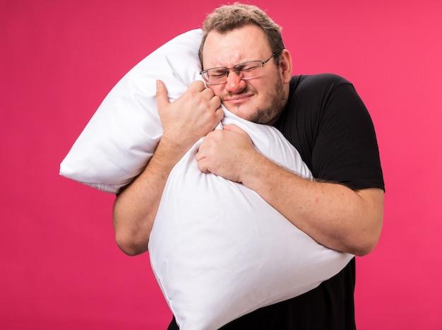 Zirytowany zamkniętymi oczami chory mężczyzna w średnim wieku przytuloną poduszkę odizolowaną na różowej ścianie