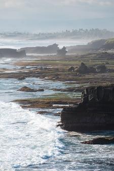 Zjawiskowy naturalny klif skalny w pobliżu świątyni pura batu bolong z falą uderzającą w linię brzegową na bali, indonezja