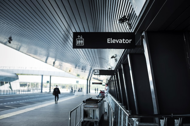 Zjazd z lotniska pulkovo w saint-petersburgu - budynek lotniska z oznakowaniem i wózkami bagażowymi oraz droga wzdłuż niego.
