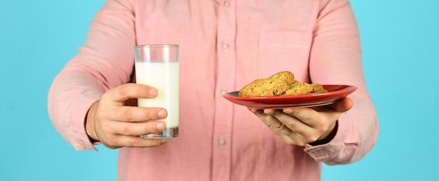 Zjedz deser ciasteczkowy. pyszne smakołyki. najlepsze jest domowe. przepis na pieczenie ciasteczek. smak dzieciństwa. męskie ręce trzymają mleko z ciasteczkami selektywnej ostrości. śniadanie lub obiad. mleczne i słodkie ciasteczka.