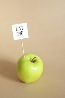 Zjedz mnie koncepcja na beżowym tle z zielonym soczystym świeżym jabłkiem i wiadomością z prośbą