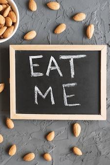 Zjedz mnie zdanie napisane na małej tablicy i surowych orzechach migdałowych