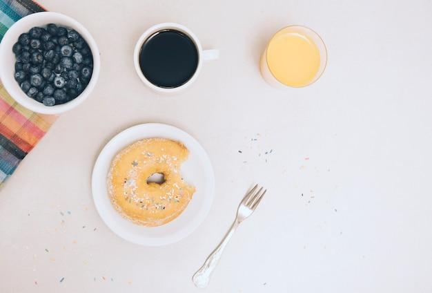 Zjedzony pączek; kawa; sok i jagody na białym tle