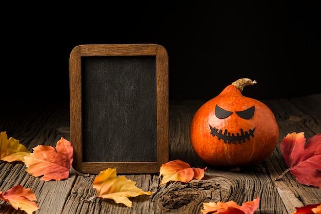 Zła dynia halloweenowa otoczona liśćmi
