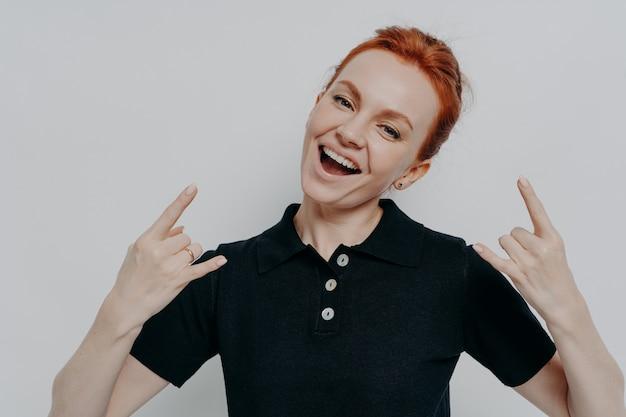 Zła dziewczyna. wesoła beztroska ruda kobieta w zwykłych ubraniach pokazująca heavy metalowy znak rocka podczas pozowania na białym tle na szarym tle w studio, uśmiechająca się do kamery rock i wykonująca gest roll