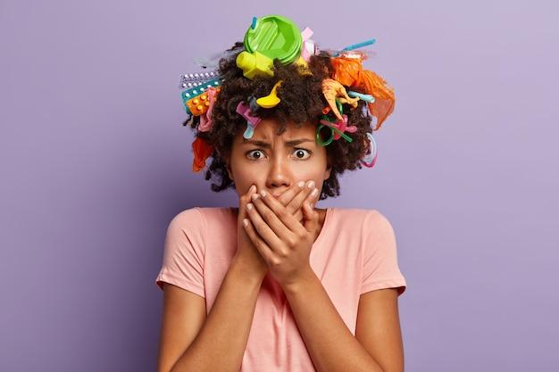 Zła kobieta pozuje ze śmieciami we włosach
