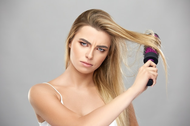 Zła kobieta szczotkuje swoje długie blond włosy ze złości, niezadowolony model szczotką do włosów na szarym tle