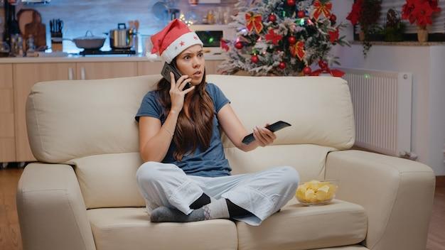Zła kobieta używająca smartfona do rozmowy służbowej na boże narodzenie