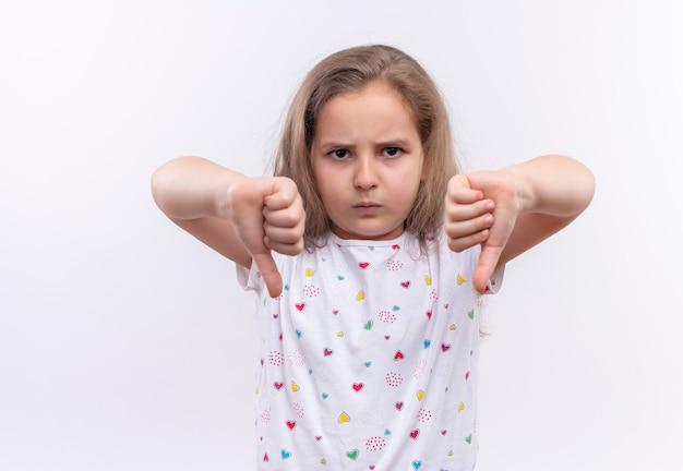 Zła mała uczennica ubrana w białą koszulkę z kciukami w dół na odosobnionej białej ścianie