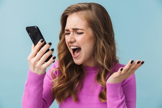 Zła młoda blondynka stojąca na białym tle nad niebieską ścianą, rozmawiająca przez telefon komórkowy