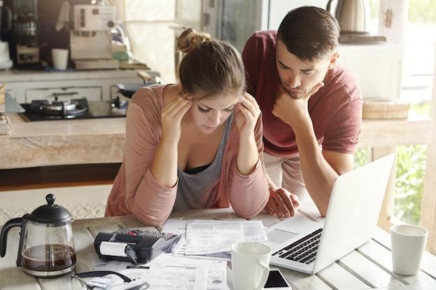 Zła młoda kobieta czuje się przygnębiona, ściska skronie, próbuje rozwiązać problemy finansowe