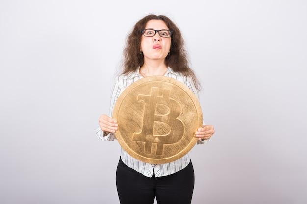 Zła młoda kobieta trzymająca duże złote bitcoiny i pokazująca język - kryptowaluta, pieniądze internetowe i