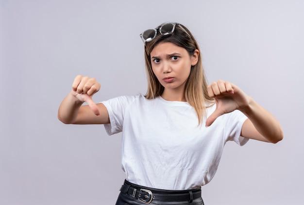 Zła młoda kobieta w białej koszulce w okularach przeciwsłonecznych, uśmiechnięta, pokazująca kciuki w dół