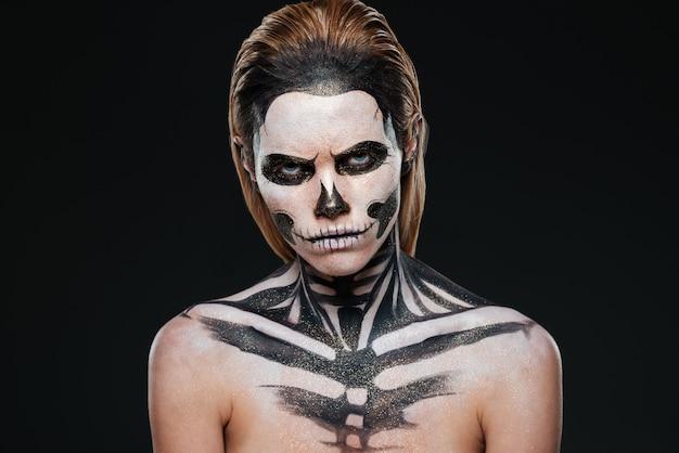 Zła młoda kobieta z gotyckim makijażem halloween na czarnym tle