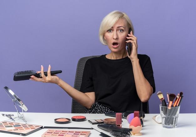 Zła młoda piękna dziewczyna siedzi przy stole z narzędziami do makijażu, mówi na telefonie trzymając grzebień odizolowany na niebieskiej ścianie