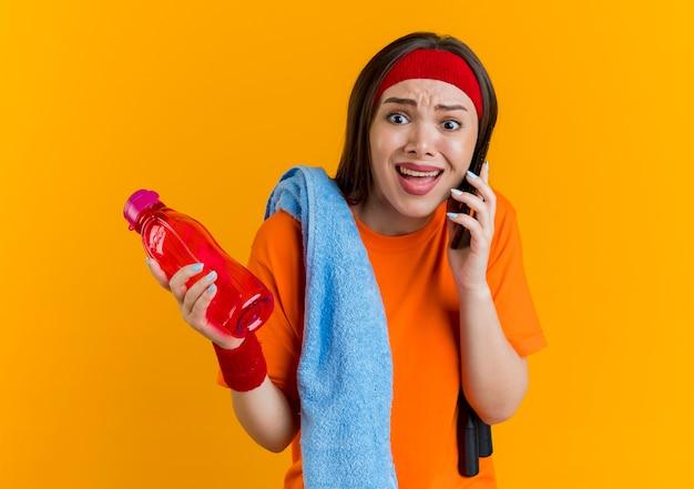Zła młoda sportowa kobieta nosząca opaskę i opaski na rękę ze skakanką i ręcznikiem na ramionach, trzymająca butelkę wody i rozmawiająca przez telefon, patrząc prosto