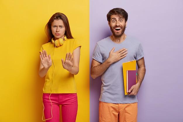 Zła niezadowolona milenialska wykonuje gest odmowy, wyciąga dłonie, marszczy brwi, jest z czegoś niezadowolona, zadowolony mężczyzna pod wrażeniem trzyma notesy, patrzy radośnie