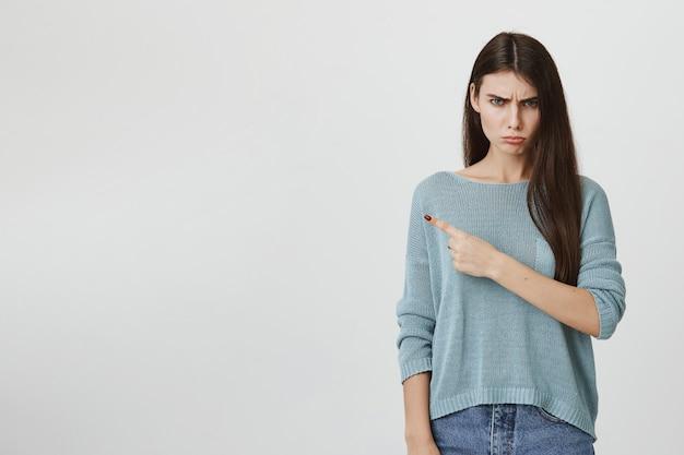 Zła obrażona dziewczyna dąsa się i wskazuje w lewo