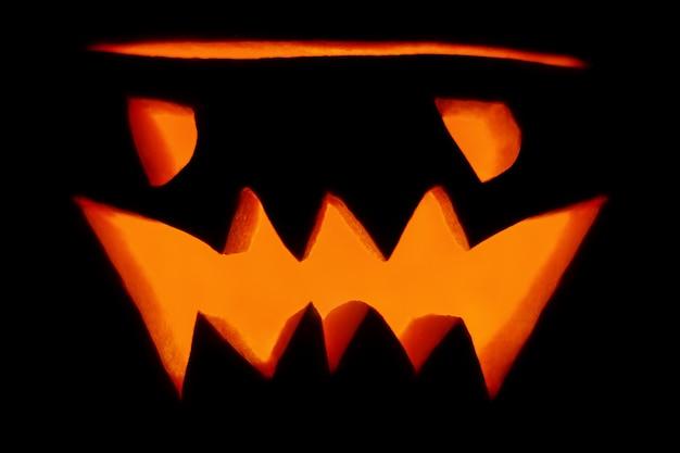 Zła pomarańczowa świecąca latarnia-jack wyrzeźbiona z dyni na wakacje halloween zbliżenie w ciemności na czarnym tle. brzydka dyniowa buzia z płonącą świecą w środku