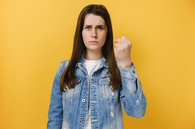 Zła poważna kobieta pokazuje zaciśniętą pięść przed kamerą