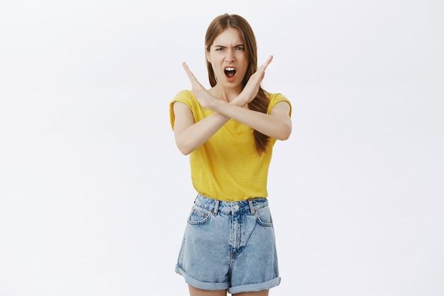 Zła, poważna młoda dziewczyna robi gest krzyża, każe przestać, mówi nie, zakazuje działania