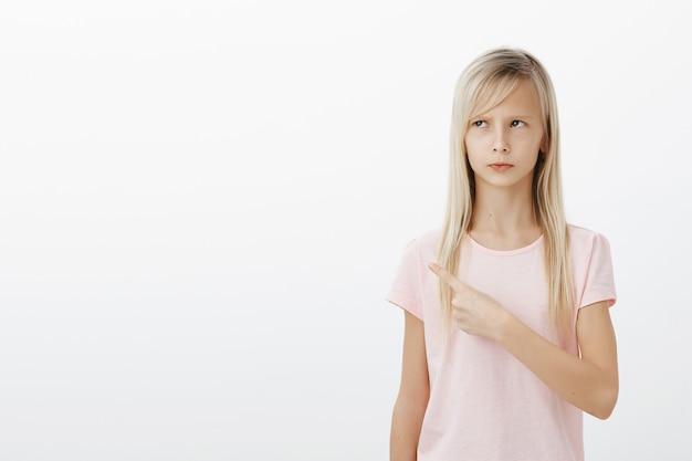 Zła słodka urażona dziewczynka wskazująca lewy górny róg, wyglądająca na zdenerwowaną