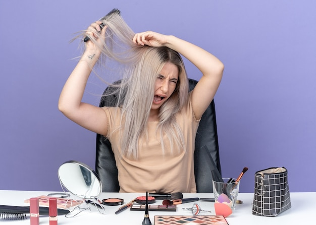 Zła z zamkniętymi oczami młoda piękna dziewczyna siedzi przy stole z narzędziami do makijażu, czesząc włosy izolowane na niebieskiej ścianie