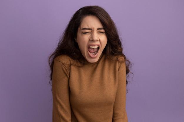 Zła z zamkniętymi oczami młoda piękna dziewczyna ubrana w brązowy sweter z golfem odizolowana na fioletowej ścianie