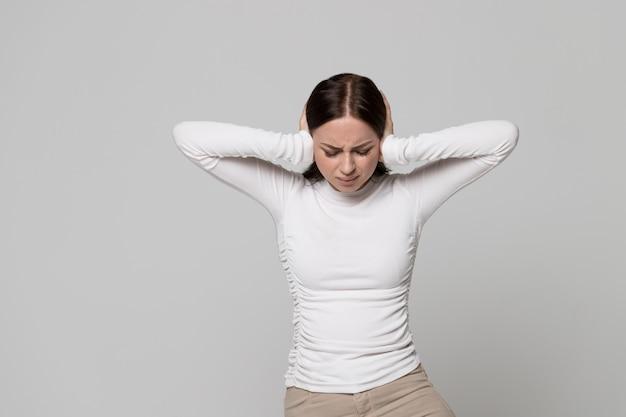 Zła zestresowana kobieta zakrywająca uszy, mająca problemy z bólem głowy przy głośnym dźwięku, hałasie